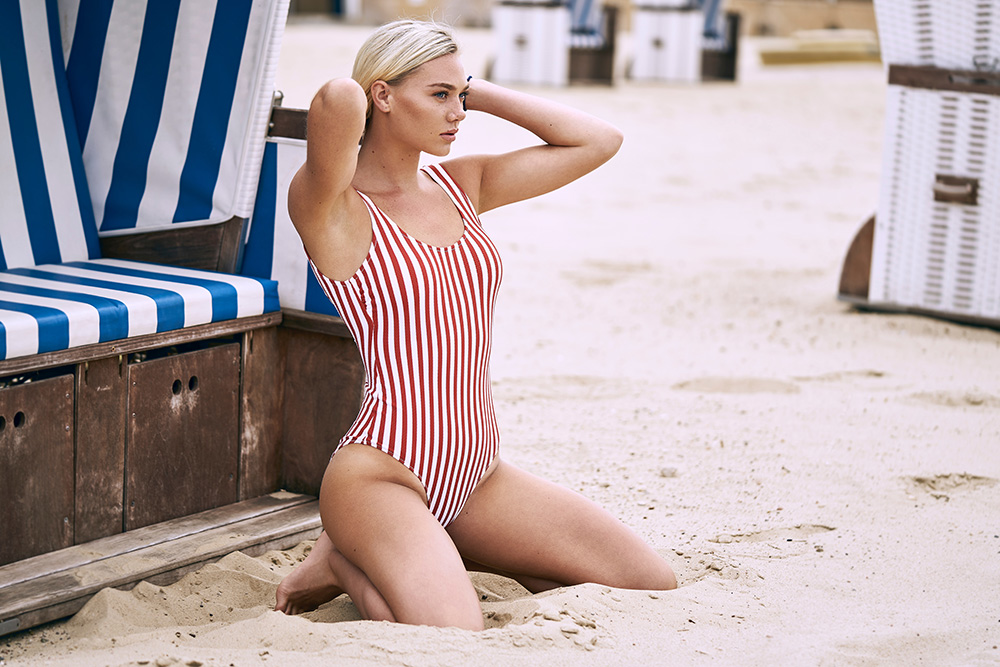 blonde with hourglass figure in red and white stripped swimsuit