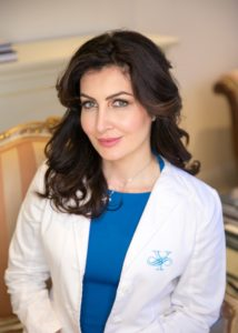 Dr. Sara Yegiyants, plastic surgeon, in a white medical coat and a blue dress