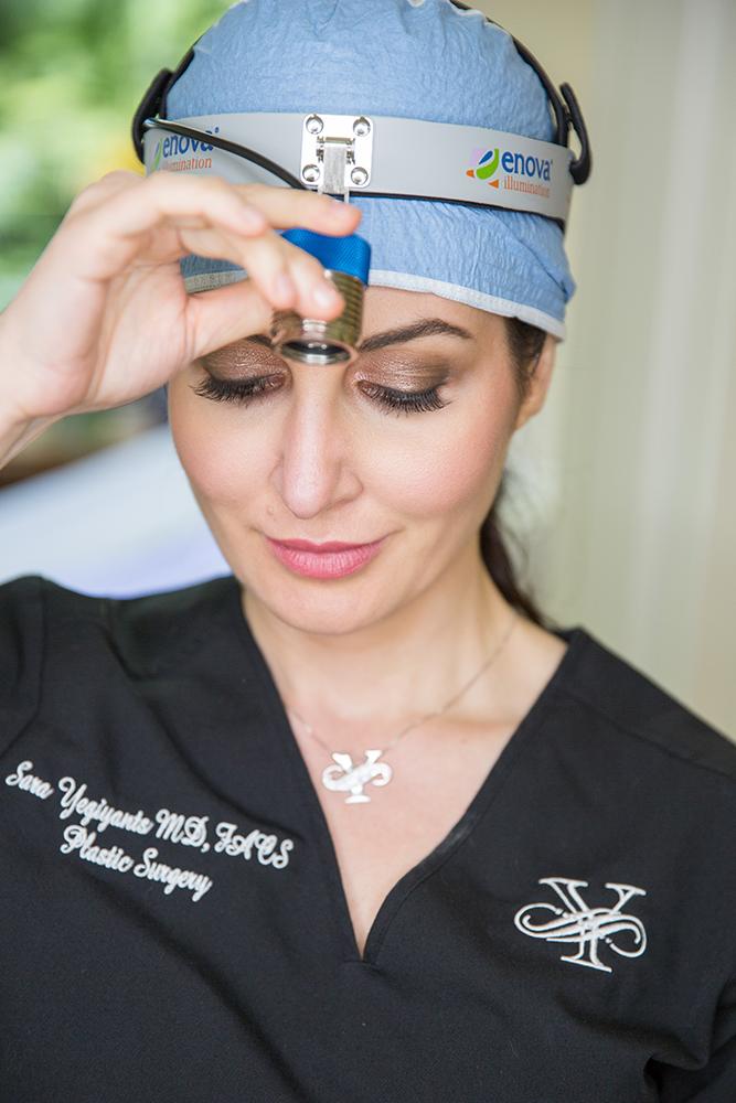 Santa Barbara plastic surgeon, Dr. Yegiyants, in black scrubs and surgical light